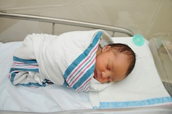 newborn baby wrapped in blanket in hospital small